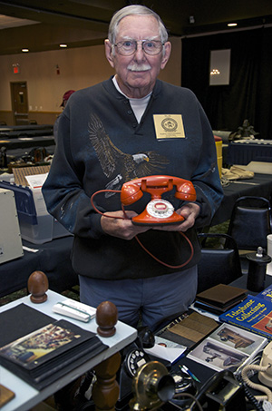 Jim Aita of Franklin, Tennessee, displays a model 202 cradle phone in Pekin red at the ---- Telephone Convention Saturday, September 13. - PHOTO BY GINNY LEE